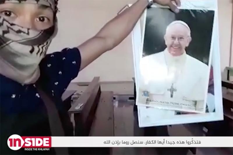 ローマ教皇フランシスコの写真を持って話す過激派組織「イスラム国」(IS)の戦闘員。戦闘員はこの後、「われわれは次はローマに行く、次はローマだ」などと言いながら、写真を破り捨てる。(写真:ISが公開した動画より)