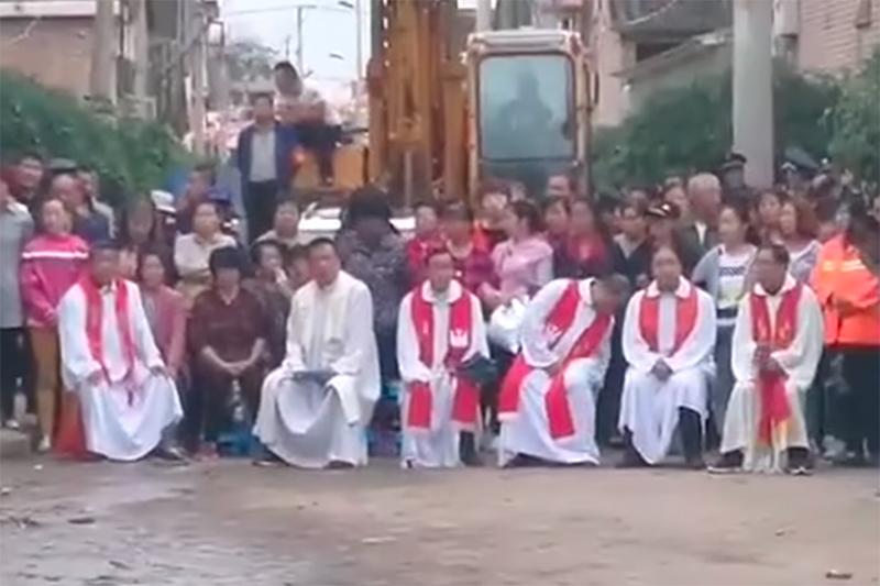 教会の取り壊しに抗議するため、ショベルカーの前で立ったり座ったりしているカトリック教会の司祭や信徒ら(写真:アジア・ニュースの動画より)