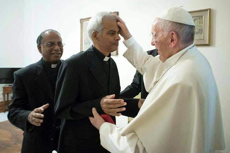解放された翌日に、バチカンでローマ教皇(右)と面会するトーマス(トム)・ウズナリル神父(中央)=13日