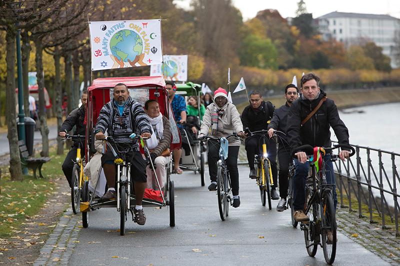 国連気候変動枠組条約第23回締約国会議(COP23)に、気候変動問題に関する宗教者からの声明を届けるため、自転車に乗って会場に向かう人々。左の男性は、フィジーから来たジェームズ・バグワン牧師。(写真:世界教会協議会=WCC / Sean Hawkey)
