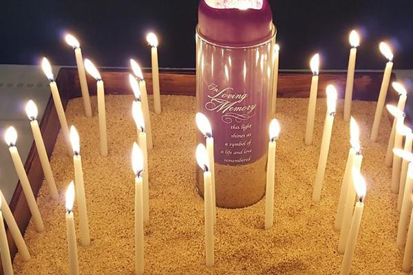 「共に信仰に生きよう」(LIFT)が今年行ったブルー・クリスマス礼拝では、亡くなった人々を覚えつつ、ろうそくに火をともした=10日、オハイオ州フレモントで