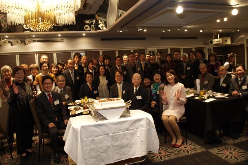 山川百合子氏(写真中央テーブル ピンク色の服)、夫の瀬戸健一郎氏(右端)と参加者=2017年12月23日、ホテルニューオータニ(東京都千代田区)で