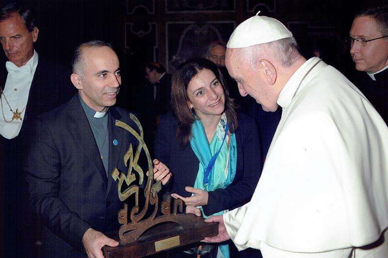 2016年にローマで諸宗教シンポジウムを開催した際、バチカンでローマ教皇フランシスコに謁見し、「慈悲の象徴」像を贈るアディアン財団のファディ・ダウ理事長(左)とナイラ・タバラ副理事長(写真:同財団)