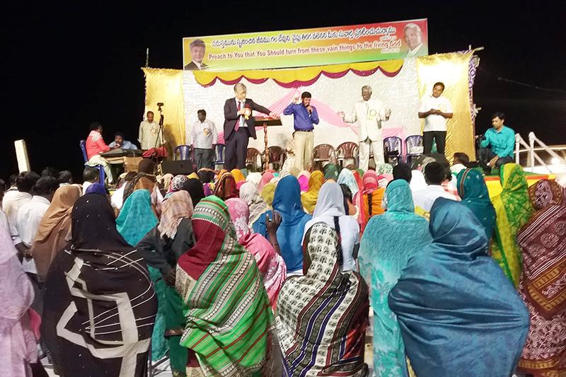 インド東部のアンドラプラデシュ州ジャゲイヤペットで行われた野外伝道集会で、集まった多くの人々を前に福音を語る万代栄嗣牧師