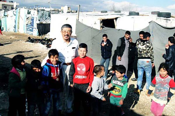 シリア国境近くのマリッシュ難民キャンプで、子どもたちに歓迎される神戸国際支縁機構の岩村義雄理事長(中央)=2017年12月30日(写真:同機構提供)