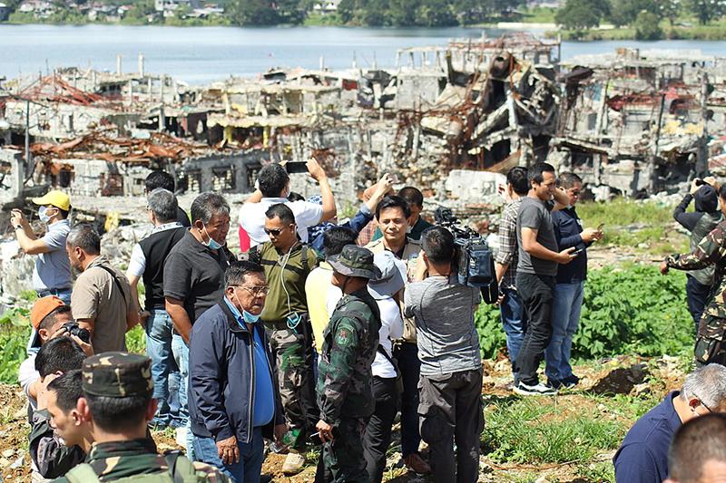 戦闘終結後、最も激しく損壊したマラウィ市内の激戦地を初めて視察する地元政府関係者。背後には廃墟と化したマラウィ市内の様子が見える=2017年11月14日(写真:フィリピン情報局)