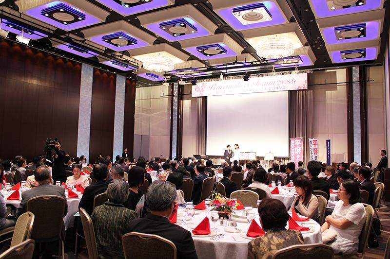 山川百合子氏のあいさつに耳を傾ける参加者たち=14日、京王プラザホテル(東京都新宿区)で