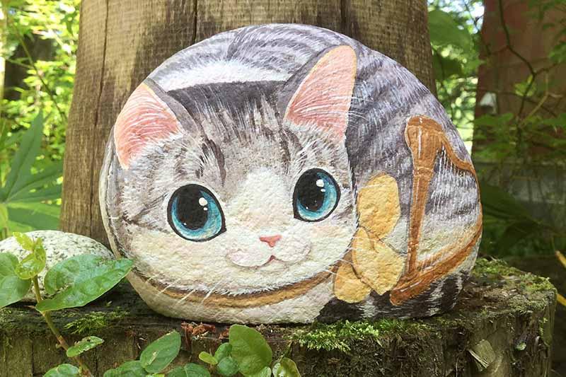 川原の丸い石に猫を描いた「石猫」。石の裏には「いつも喜んでいなさい」「すべてのことを感謝しなさい」と聖書の言葉が書かれている。<br />