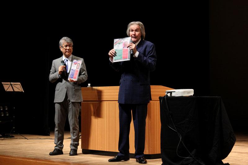 実際に助けを必要とする子どもたちの写真を見せながら、メトロ・ワールド・チャイルドの働きを紹介するビル・ウィルソン氏(右)=6日、日本橋公会堂(東京都中央区)で