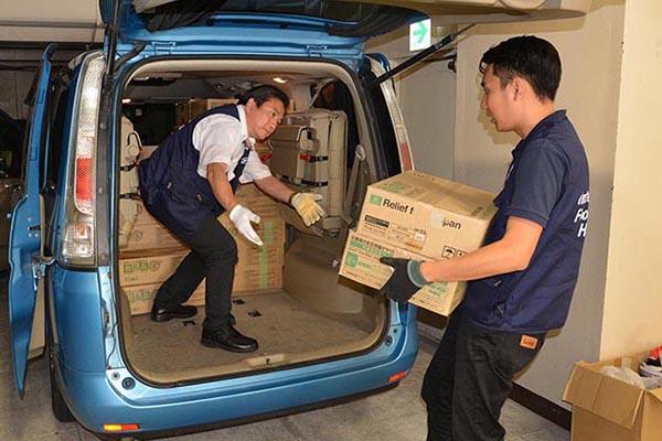 パンの缶詰約800食分を車に積み込む日本国際飢餓対策機構(JIFH)のスタッフ=9日(写真:同機構)