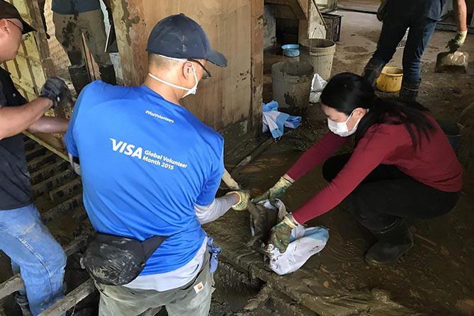 家に流れ込んだ土砂をかき出すボランティアたち(写真:日本国際飢餓対策機構)