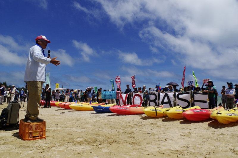 辺野古の米軍キャンプ・シュワブに隣接する松田ヌ浜で行われた土砂搬入反対集会。約450人が参加し、ヘリ基地反対協議会の安次富浩共同代表(左手前)が、土砂搬入を許さず、知事選にも必ず勝とうと呼び掛けた=8月17日(写真:山本英夫撮影、ブログ「<a href='http://ponet-yamahide.cocolog-nifty.com/' target='_blank'>ヤマヒデの沖縄便りⅢ</a>」より許可を得て転載)<br />