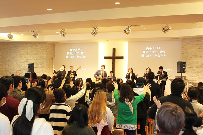 ワーシップ!ジャパン宣教人財育成学院が主催する「ワーシップ・ジャパン・カンファレンス2018」の賛美集会で、手を上げて賛美をささげる参加者たち=3月17日、神の家族主イエス・キリスト教会(東京都足立区)で