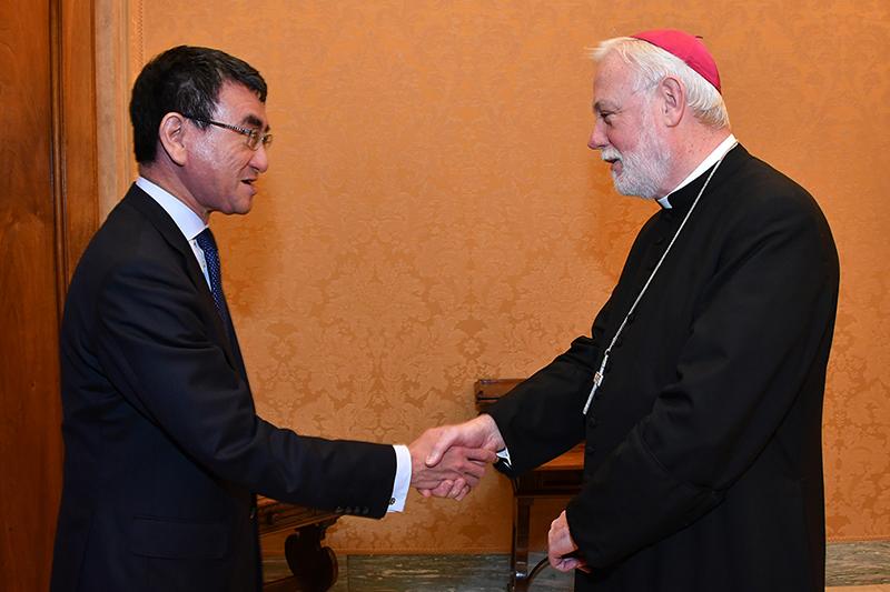 握手する河野太郎外相(左)と、バチカン(ローマ教皇庁)国務省外務局長(外相)のポール・リチャード・ギャラガー大司教=23日、バチカンで(写真:外務省提供)<br />