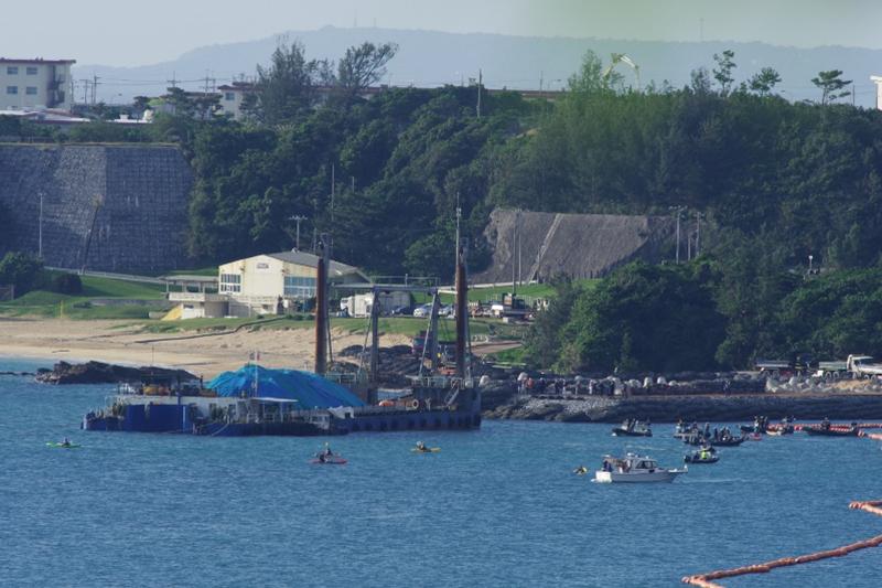 辺野古海域へ投入する土砂を運ぶ土砂運搬船。抗議のカヌーが周辺に見える。土砂はブルーシートで覆われており、運搬船はこの後接岸し、重機が船の上に乗って作業を始めた。陸地には土砂を積んだダンプカーの列も見える=14日午前9時ごろ(写真:山本英夫撮影、ブログ「<a href='http://ponet-yamahide.cocolog-nifty.com/' target='_blank'>ヤマヒデの沖縄便りⅢ</a>」より許可を得て転載)<br /> <br />