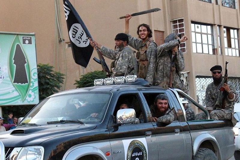 """「イスラム国」(IS)の旗や武器を持って町の中を車で移動するISの戦闘員たち=2014年(写真:The """"futurist"""" aesthetics of ISIS)"""