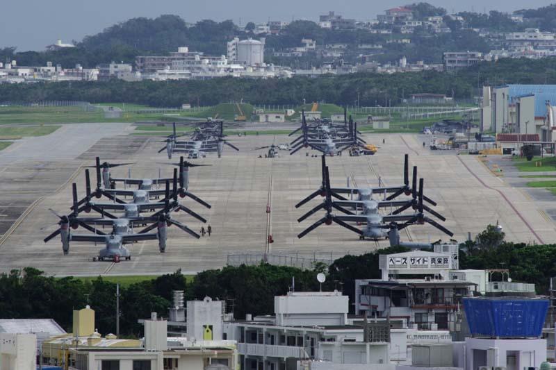 米軍普天間飛行場(沖縄県宜野湾市)に並ぶオスプレイや大型輸送ヘリCH53。沖縄戦の激戦地となった嘉数(かかず)高台から見た眺め=2月22日撮影。日本政府は、名護市辺野古への移設が普天間飛行場の危険除去の唯一の解決策だと主張しているが、2月24日に実施された沖縄県民投票では、辺野古における米軍基地建設のための埋め立てに7割以上が反対票を投じた。(写真:山本英夫撮影、ブログ「<a href='http://ponet-yamahide.cocolog-nifty.com/' target='_blank'>ヤマヒデの沖縄便りⅢ</a>」より許可を得て転載)<br />