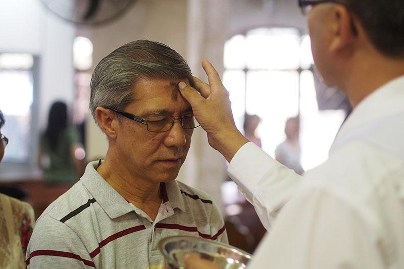 レントの初日である「灰の水曜日」に、額に灰で十字の印を付けてもらう男性信者(写真:John Ragai)