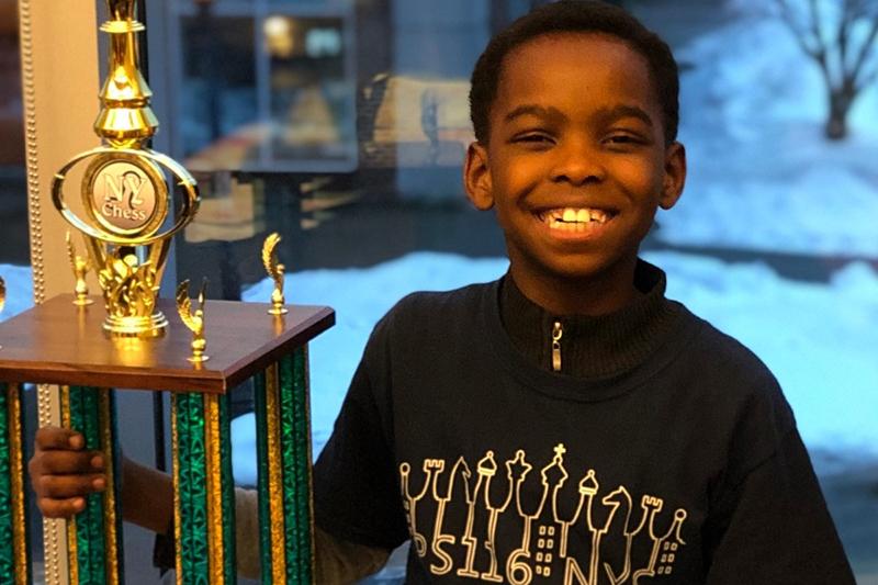 チェス大会の優勝トロフィーを持って満面の笑顔を見せるタニトルワ・アデウミ君(写真:ゴーファンドミーのサイトより)