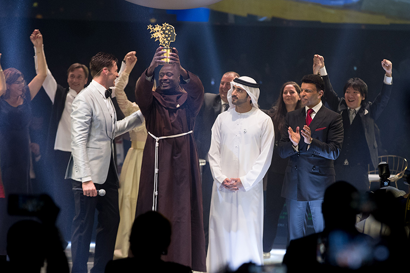 受賞トロフィーを持って喜ぶ、フランシスコ会の修道士で、ケニアの中学教師であるピーター・タビチさん(中央)。後ろには、日本から選ばれた立命館小学校(京都市)の英語教師である正頭英和(しょうとう・ひでかず)さん(右端)ら、他の最終候補者が立っている=23日、アラブ首長国連邦(UAE)・ドバイで(写真:世界教育スキル・フォーラム)