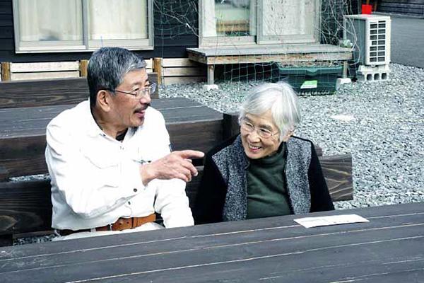 福岡県朝倉市林田の仮設住宅で梶原ミドリさん(右)から話を聞く筆者=2月18日