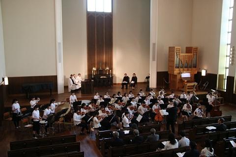 1日午後にプール学院(大阪市生野区)の礼拝堂「清心館」で行われた同学院主催の記念礼拝で演奏する同学院中学校・高校の吹奏楽部と弦楽部の生徒たち(写真:同学院提供)<br />