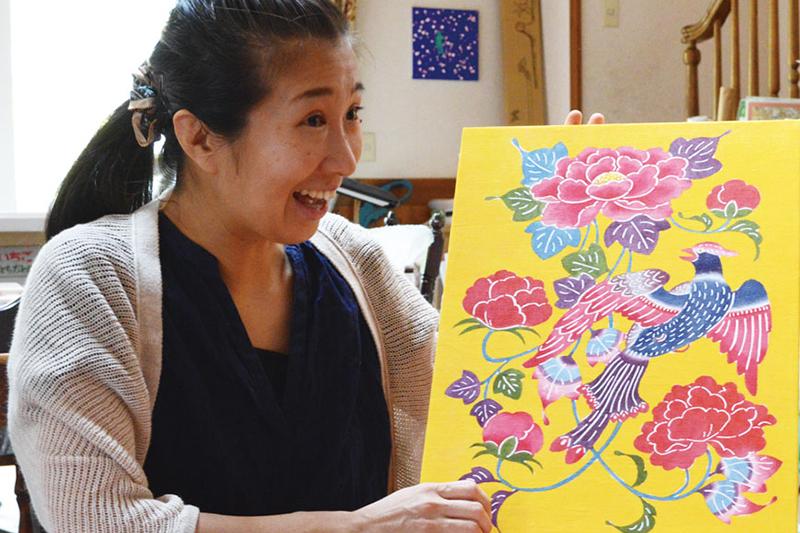 沖縄の伝統工芸「紅型(びんがた)」の魅力を語る田口恵さん。作品は、琉球王朝で王族のみに使用が許されていた黄色を背景に、ボタンとオナガドリの古典柄をあしらったもの。<br />
