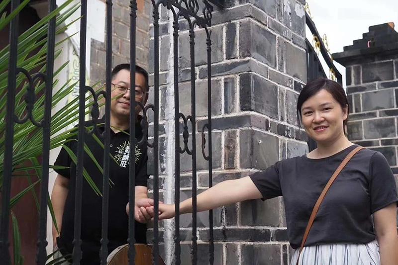 柵越しに手を握り合う秋雨聖約教会の王怡(ワン・イー)牧師と妻の蒋蓉(ジャン・ロング)さん(写真:同教会のフェイスブックより)