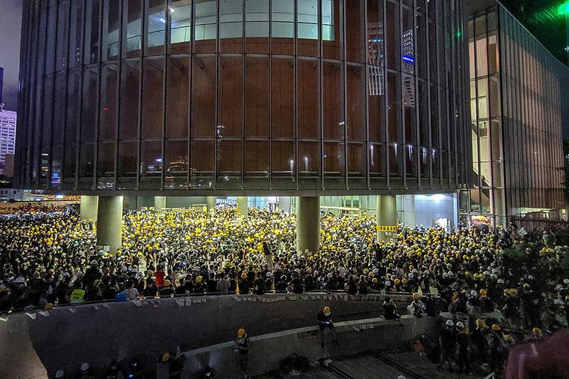 香港の立法会(議会)近くで、防護用のヘルメットをかぶりながら抗議する人々=1日夜(写真:Studio Incendo)