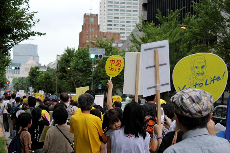 国会議事堂の近くをデモ行進する参加者たち=15日