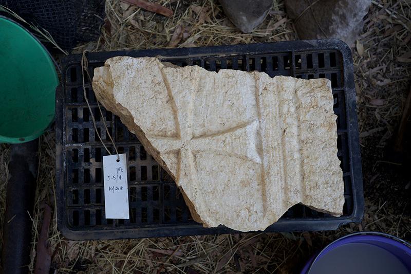 ガリラヤ湖北岸のエルアラジ遺跡で発見された十字架をあしらった教会の壁と見られる石片(写真:米ナイアック大学古代ユダヤ教・キリスト教起源研究センター)<br />
