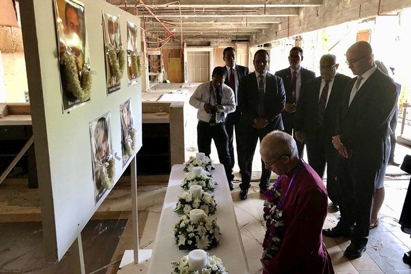 テロの犠牲者の写真を前に祈りをささげるカンタベリー大主教ジャスティン・ウェルビー(写真:ウェルビー氏のツイッターより)<br />