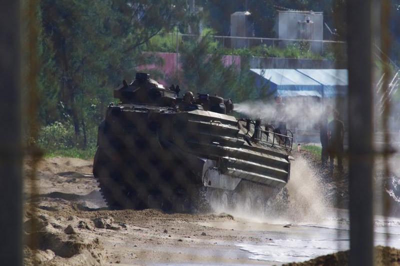 フェンスの奥で軍事演習を繰り返す水陸両用装甲車。この辺野古の渚(なぎさ)・海が戦場につながるのだ=9月16日(写真:山本英夫撮影、ブログ「<a href='http://ponet-yamahide.cocolog-nifty.com/blog/' target='_blank'>ヤマヒデの沖縄便りⅢ</a>」より許可を得て転載)