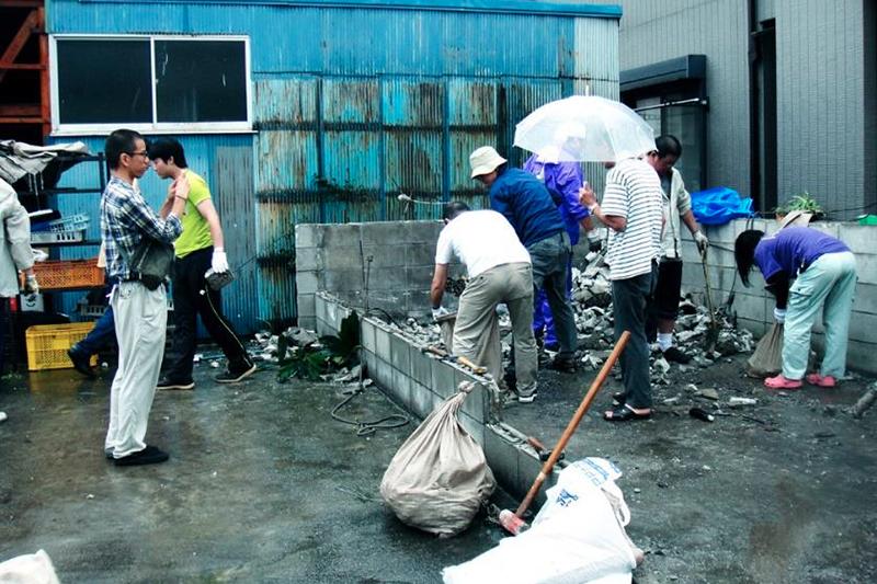 雨が降る中、台風15号により崩れた千葉市今井にある倉庫のがれき撤去作業を行う神戸国際支縁機構のボランティアたち。100回目となる東北ボランティアに向かう途上、千葉市の他、被害の大きかった南房総の幾つかの自治体を訪れ、1回目となる千葉災害ボランティアを行った。(写真:同機構提供)<br />