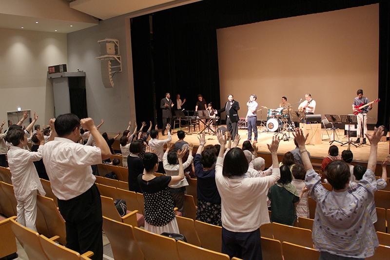 「神様と顔と顔を合わせる働き2019 神様の御顔を仰ぐ 癒しと奇跡の集会」で手を上げて神を賛美する参加者たち=8月16日、なかのZERO(東京都中野区)で