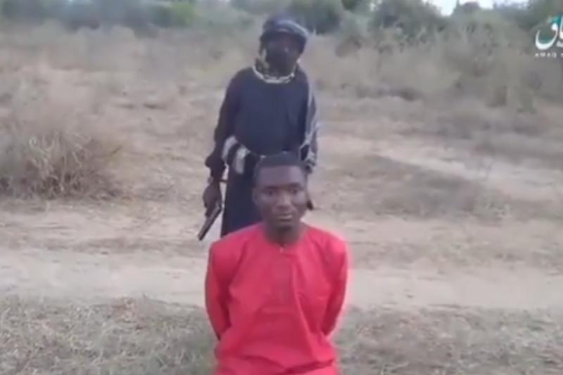キリスト教徒の大学生ラプビル・ダシア・ダレプさんを前に拳銃を持って立つイスラム過激派の少年兵(画像:アマク通信が公開した映像より)