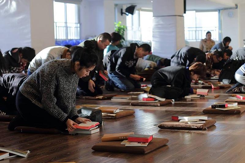 聖書を読みながら座って祈る秋雨聖約教会(中国四川省成都)の教会員たち。同教会は「家の教会」と呼ばれる政府非公認のプロテスタント教会で、2018年12月に牧師や教会員ら100人以上が拘束され、創設者の王怡(ワン・イー)牧師は19年12月、国家政権転覆扇動などの罪で懲役9年の判決を言い渡された。(写真:同教会のフェイスブックより)<br />