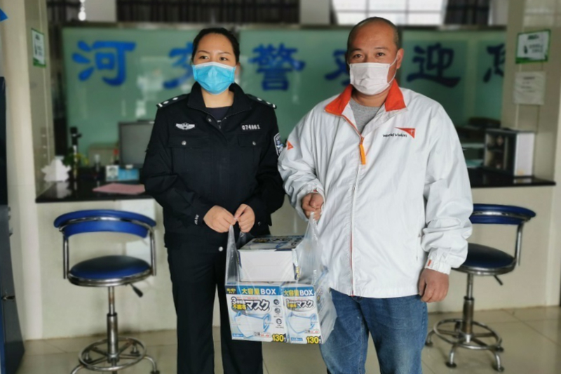 マスクの箱を持つワールド・ビジョンのスタッフ(右)(写真:ワールド・ビジョン)