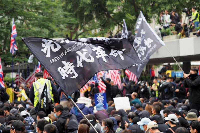 「光復香港、時代革命(香港を取り戻せ、革命の時だ)」というスローガンを掲げてデモを行う香港の人々。昨年11月、香港における人権尊重や民主主義の確立を支援する「香港人権・民主主義法」を成立させた米国や、かつての宗主国である英国の国旗を掲げる人々もいる=1月19日(写真:Etan Liam)