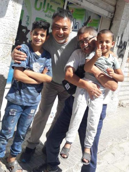 ヨルダン現地の子どもたちと。右が豊田幹夫さん、左が村上則貴さん。「現地の子どもは明るく人なつっこい」という。