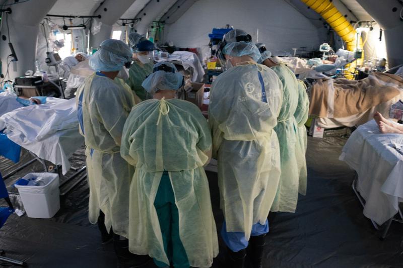 キリスト教慈善団体「サマリタンズ・パース」がイタリア北部クレモナに設置した救急野外医療施設で、新型コロナウイルス感染症患者のために祈る医師や看護師たち(写真:サマリタンズ・パース)