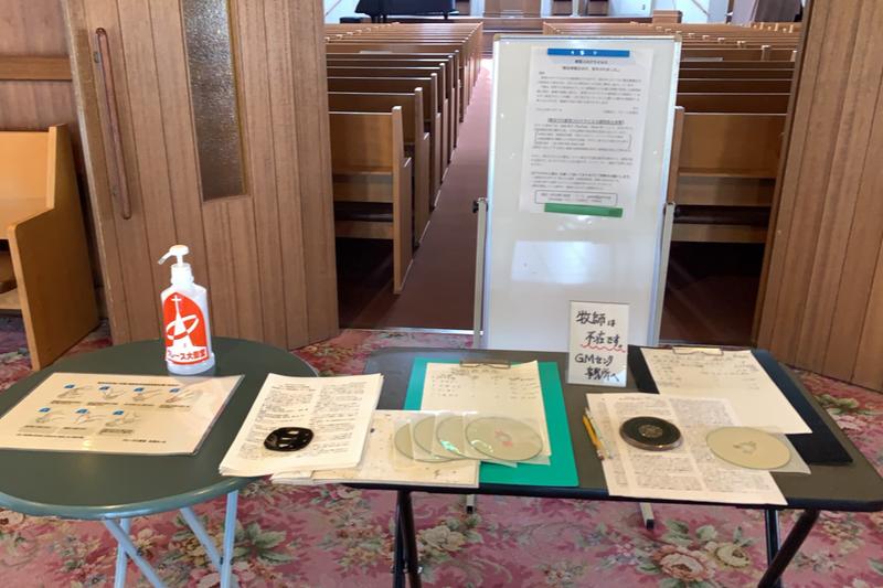 礼拝堂の入り口前。手指消毒のためのエタノール消毒液や礼拝の録音CDなどを置いている。