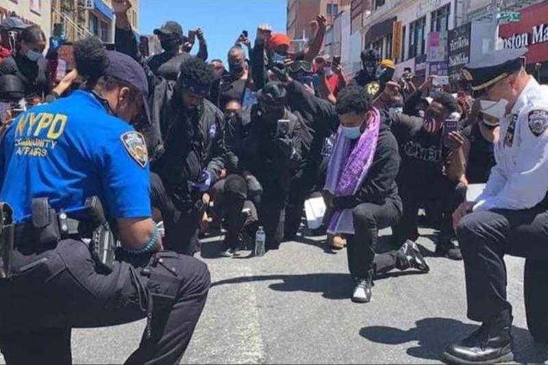 ニューヨークの警官たちと共に祈るガレリー・K・ソロモン牧師(紫色のスカーフの男性)とエクセリング教会の信徒たち(写真:Dr. Te Bassett)