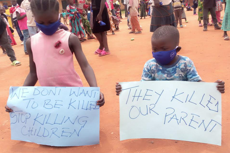 「私たちは殺されたくない。子どもを殺すのをやめて」「彼らは私たちの両親を殺した」と書かれた紙を掲げる子どもたち(写真:インターソサイエティー)