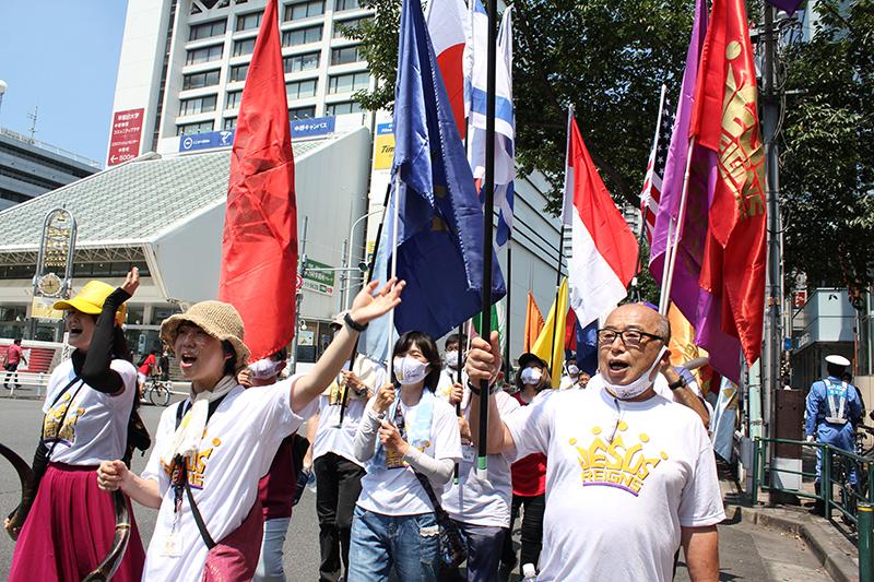 「イエス・キリストが日本の統治者である(ジーザス・レインズ・ジャパン)」ことを宣言し、主を賛美しながら中野サンプラザ(東京都中野区)の前を行進するパレードの参加者たち=15日