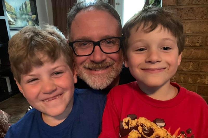 男の子の服を着て父親と双子の兄弟と共に微笑むジェームズ君(右)=7月29日(写真:「ジェームズ君を救え」フェイスブックページ)