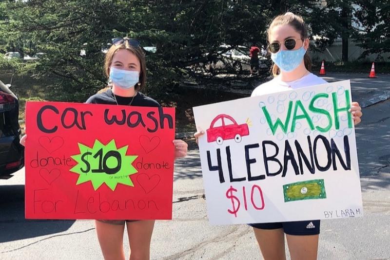 レバノンの爆発被災者支援のために洗車をしていることをボードで知らせるボストン聖ジョージ正教会の青年たち=22日(写真:同教会のティモシー・J・ファーガソン神父)<br />