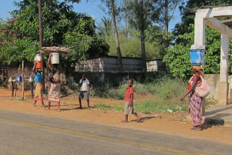 子どもを連れ、荷物を頭の上に乗せて運ぶモザンビークの女性たち=2011年(写真:fabulousfabs)