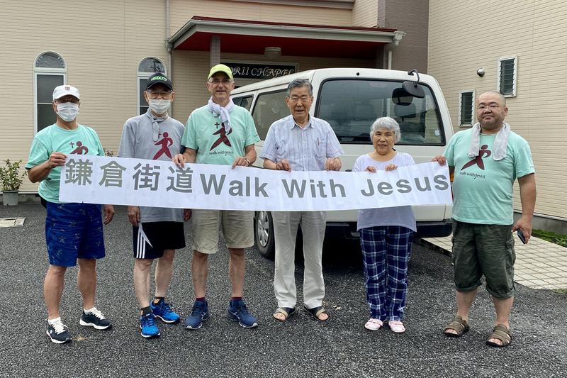 出発前に「鎌倉街道 Walk With Jesus」の垂れ幕を掲げる参加者たち=10日、日本リバイバル連盟寄居チャペル(埼玉県寄居町)で