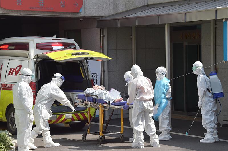 韓国南部の釜山で、新型コロナウイルスの患者を病院に運び込む医療スタッフ(写真:釜山広域市)